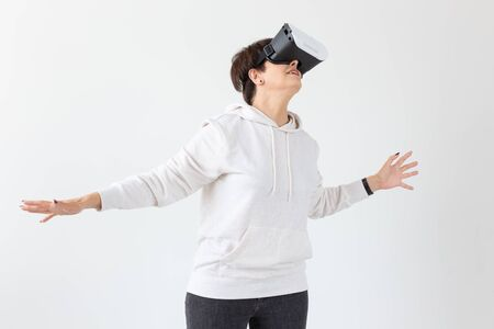 Unidentified middle-aged woman in a light sweater plays a 3D game with glasses of virtual reality on a white background. High technology concept for older people.