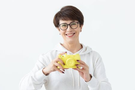 Positive middle-aged woman in glasses holds in hand a vintage yellow camera posing on a white background. Concept of photo lovers and hobbies