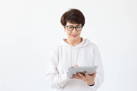 Cute middle-aged woman in casual clothes is looking online stores using a tablet on a white background. Concept of wireless internet and online shopping. Copyspace. Banco de Imagens