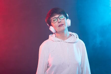Beautiful middle-aged woman in a white sweater and glasses is listening to music while posing on a red-blue background in a studio. The concept of a favorite hobby. Advertising space. Banco de Imagens