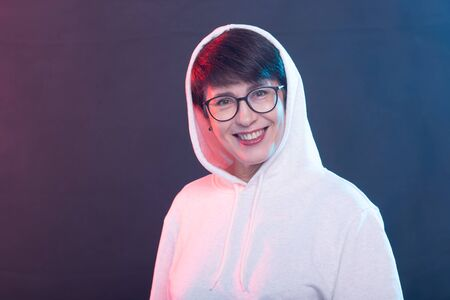 Portrait of a cheerful pretty woman in a light sweater and glasses posing on a blue background. The concept of a positive middle-aged woman. Advertising space. Stock Photo