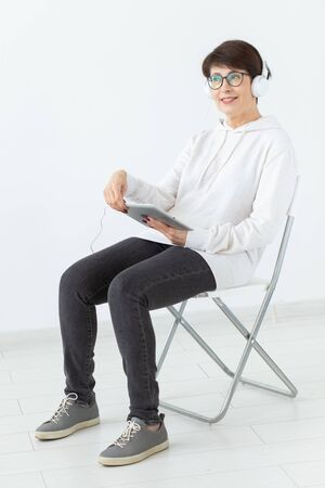 Charming slim middle-aged woman in glasses and a sweater sits on a chair and listens to her favorite online radio with the help of a headset and wireless internet on a white background