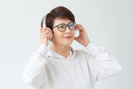 Cute positive middle-aged woman in sweater and glasses is listening to music with wire headphones standing on a white background. Concept of hobbies and subscriptions to favorite radio station. Banco de Imagens