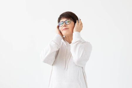 Pretty keen middle-aged woman in glasses and a white sweater listens to her favorite music with headphones on a white background. Online radio and music subscription concept. Banco de Imagens