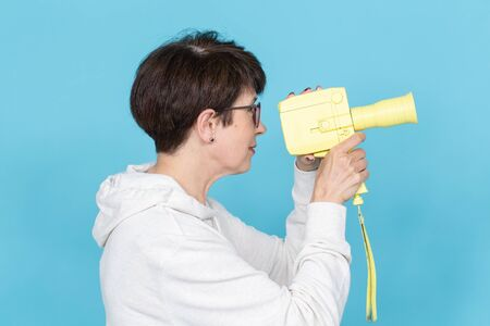 Side view of a middle-aged woman with a short haircut in a sweater and glasses holding a yellow vintage movie camera. Concept of video shooting