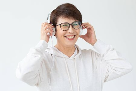 Beautiful woman 40-50 years old listening music in big headphone on white background