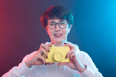 Photographer, art and hobbies concept - Woman 50 years old hold in hand yellow vintage camera on colourful background