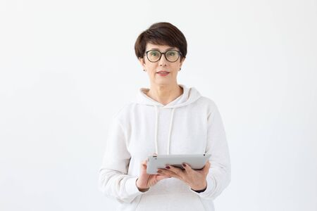 Technologies and modern people concept - Beautiful woman 50 years old with short hair holding tablet on white background Stock Photo