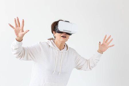 Modern technologies, future and people concept - Woman 40-50 years old wearing virtual reality glasses on white background
