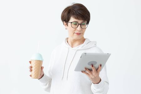 Beautiful woman 50 years old with short hair holding tablet and drinking cocktail from funny shaker on white background Stock Photo