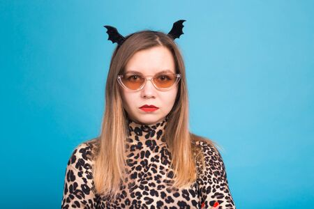 The evil woman with a waist bat on the head. Fancy dress for Halloween on blue background Stock Photo