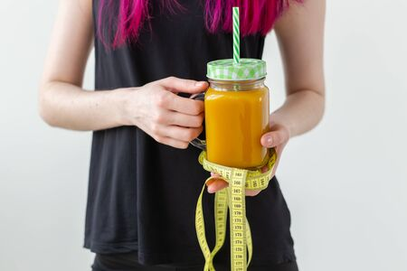 Unidentified young girl hipster holding a fruity protein juice with a straw and measuring tape. Conception of healthy nutrition and good fitness.
