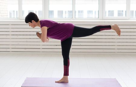 Healthy lifestyle, people and sport concept - Middle aged woman doing yoga