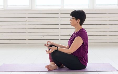 Sport, yoga, people concept - Sporty middle-aged woman practicing yoga indoors 写真素材