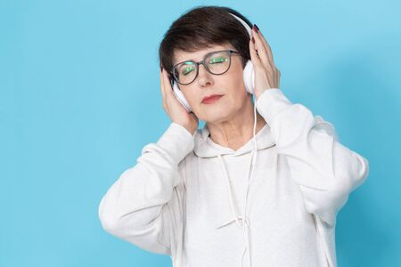 Beautiful woman 40-50 years old listening music in big headphone on blue background. Stock Photo