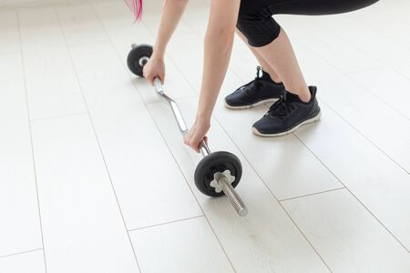 Unidentified young girl raises barbell in the spacious bright gym to perform exercises. Concept of strong muscles and a healthy body.