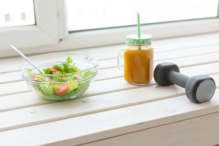 Vegetable salad fruit smoothies and dumbbell lie on a white windowsill. Concept of healthy lifestyle physical activity and proper nutrition.