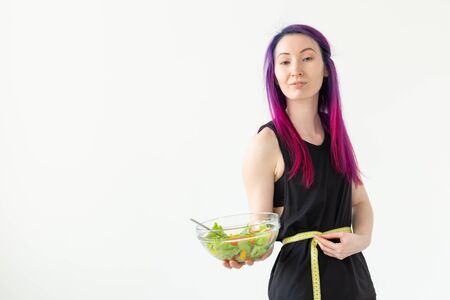 Slim young asian girl with colored hair is measured hanging a measuring tape and holding a light vegetable salad in her hands posing on a white background. Healthy eating concept. Copyspace. Banque d'images