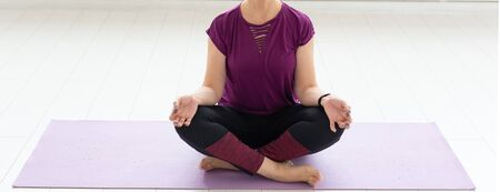Healthy lifestyle, people and sport concept - Close up of middle age woman practicing yoga in lotus pose