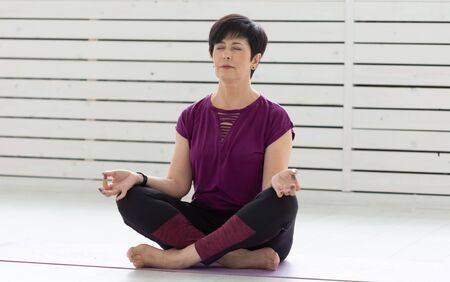Healthy lifestyle, people and sport concept - Attractive middle age woman practicing yoga in lotus pose Banco de Imagens - 124851950
