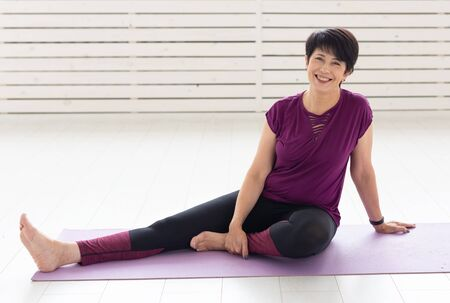 People, yoga, sport and healthcare concept - Relaxed smiling middle-aged woman sitting on exercise mat over white background Banco de Imagens - 124852087