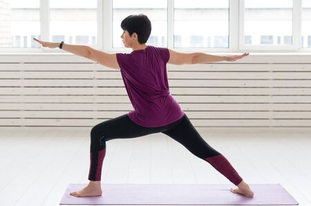 People, yoga, sport and healthcare concept - Middle-aged woman standing in Warrior over white background Banco de Imagens - 124852088