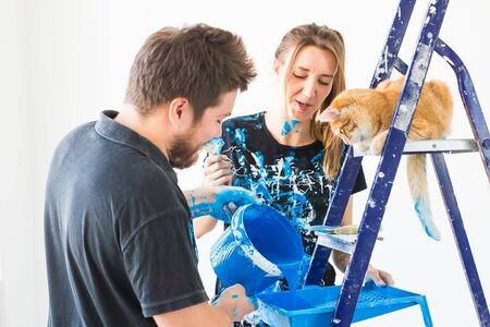 Repair, renovation, pet and love couple concept - young family with cat doing repair and painting walls together and laughing