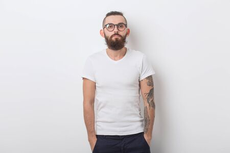 Beauty, fashion and people concept - Cool man with beard posing over white background