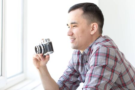Vintage, photographer and people concept - handsome asian man with retro camera indoors