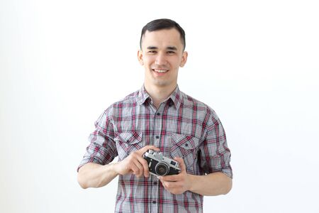Vintage, photographer and people concept - handsome asian man with retro camera over white background Stock Photo