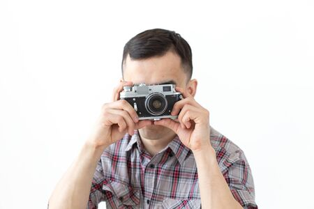 People hobby and leisure concept - young asian man using his vintage camera on white background Banco de Imagens