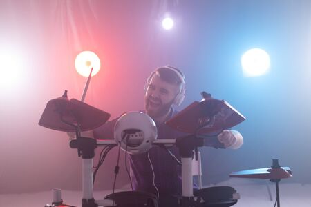 People, music and hobby concept - emotional man playing drums on the stage.