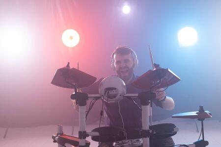 People, music and hobby concept - emotional man playing the electronic drums on the stage