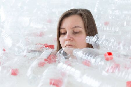 Dehydrated sick woman is lying in a pile of plastic bottles. Environmental pollution problem. Stop nature garbage environment protection concept Reklamní fotografie
