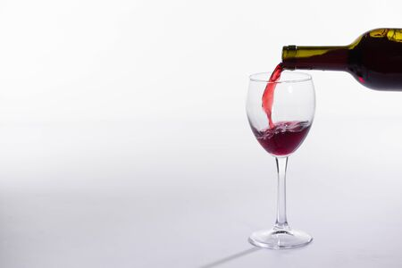 Red wine bottle pour glass on white background with copy space Reklamní fotografie