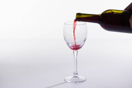 Red wine pouring from bottle into big glass on white background with copy space