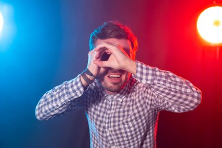 Young bearded hipster man with his hands depicts a telescope posing on a red-blue background. The concept of information retrieval and the applicant. 스톡 콘텐츠 - 124854258