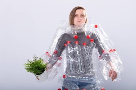 Dehydrated sick woman is standing with dress in plastic bottles holding green plant. Environmental pollution problem. Stop nature garbage environment protection concept