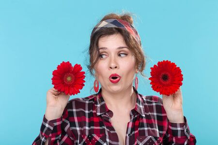 Close-up portrait of a beautiful young surprised woman holding red flowers with different hearts in the hands posing on a blue background. Concept of differences and delicate nuances.