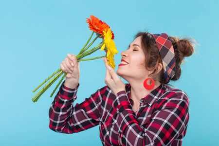 Beautiful positive young woman in a plaid shirt and a bandage sniffing beautiful bright gerbera flowers posing over a blue background. Concept of gifts and greetings. Imagens - 124880652