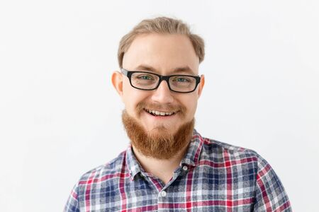 Positive emotions and people concept - young bearded man in glasses is smiling on white background
