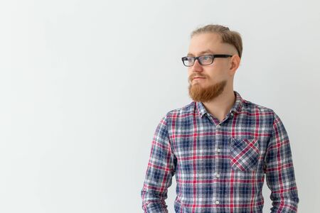 Portrait of thoughtful light blonde man with red beard over white background with copy space