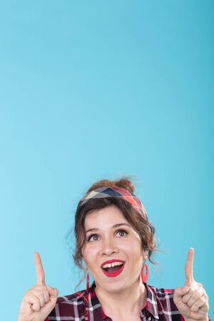 Positive pretty young woman with red earrings joyfully shows her finger upwards posing on a blue background. Concept information and link above. Copyspace.
