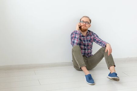 Bearded man sitting on the floor and talking on the phone, light background with copy space