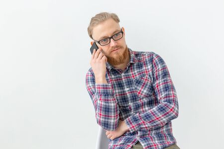 Bearded handsome man talking on the phone over white background