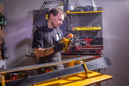 A man in work clothes repairman in the workshop ski service repairing the ski Фото со стока