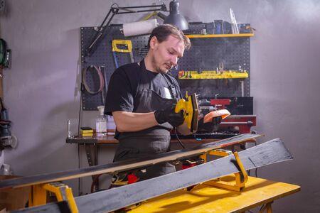 Repair, people concept - mechanic, man is rubbing a ski Фото со стока