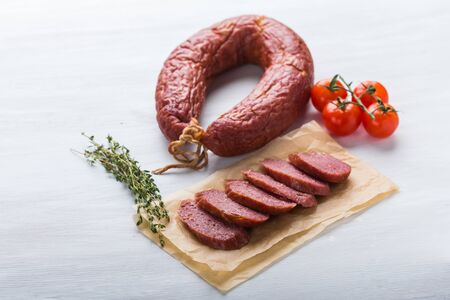 Food, meat and delicious concept - sausages made with horse meat with species and vegetables
