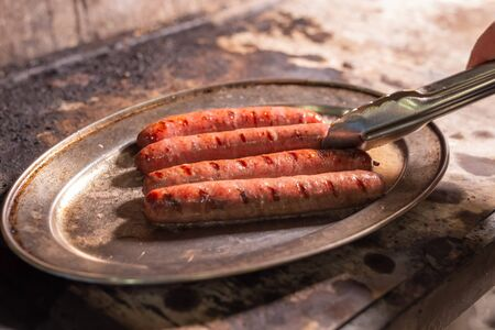 food, delicious and meat concept - roasting horse meat sausages grilled.