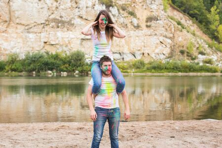 Festival holi, summer tourism and nature concept - young attractive woman sitting piggyback on her boyfriend on nature Stock Photo